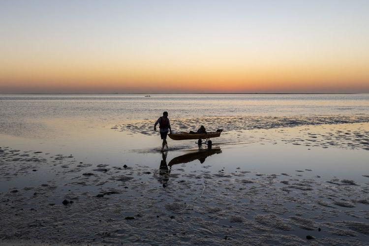 Man carrying woman sitting boat at shore