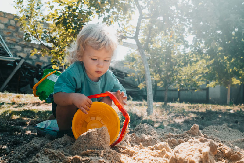 Boy playing with sand in yard