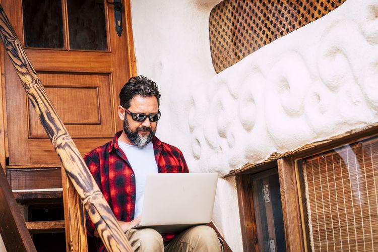 Man using laptop while sitting on steps
