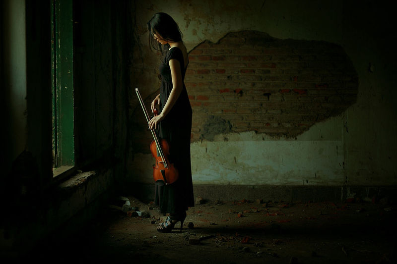 Side view of woman holding violin standing in old home