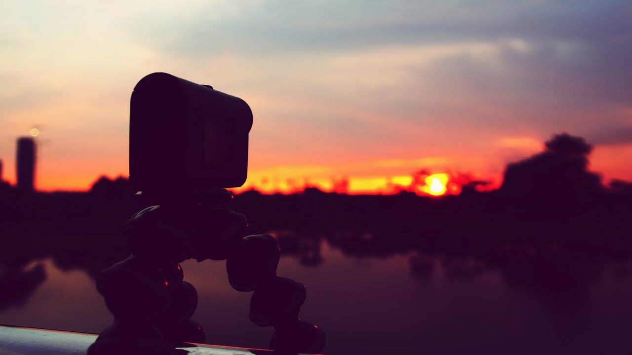 Close-Up Of Silhouette Camera By River Against Sky During Sunset