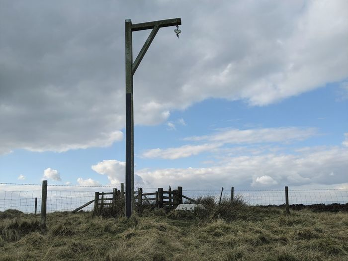 Wooden posts on field against sky
