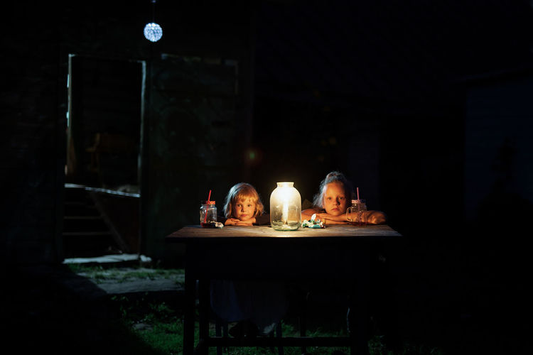 two Children Adult Candle Child Childhood Children Only Children Photography Dark Electric Lamp Food And Drink Glass Household Equipment Illuminated Indoors  Lighting Equipment Nature Night People Table Two People