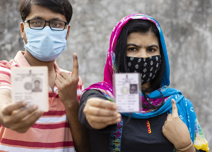 A man and woman showing ink-marked finger and voter card with safety nose mask on