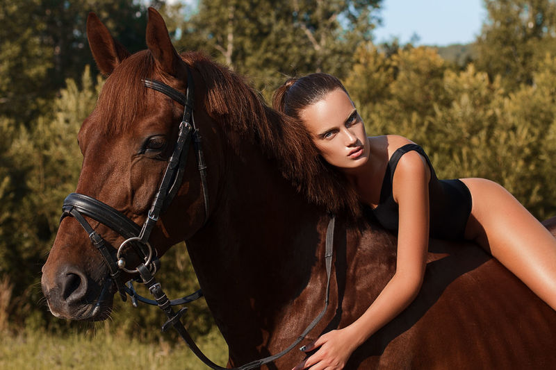 Portrait of beautiful woman riding brown horse on field
