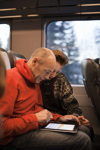 Man looking at camera while sitting in train