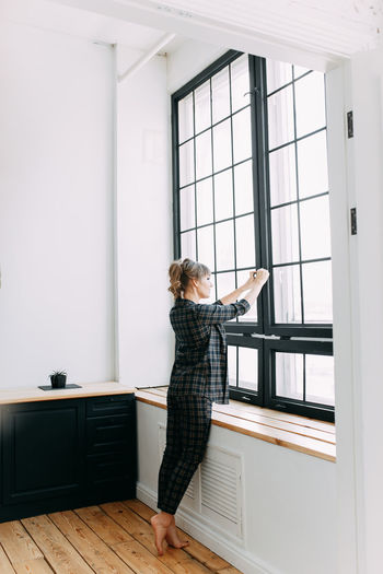 Girl in a business suit and glasses stands working near the window at home, in the office