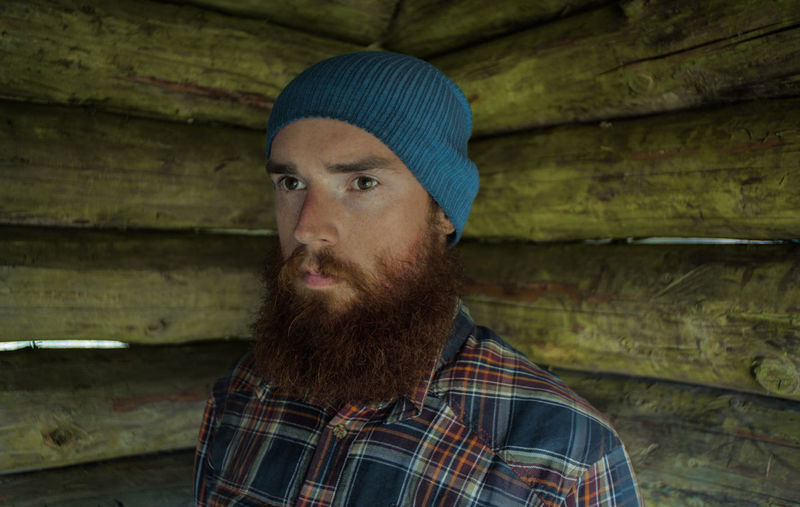 Bearded man by wooden wall