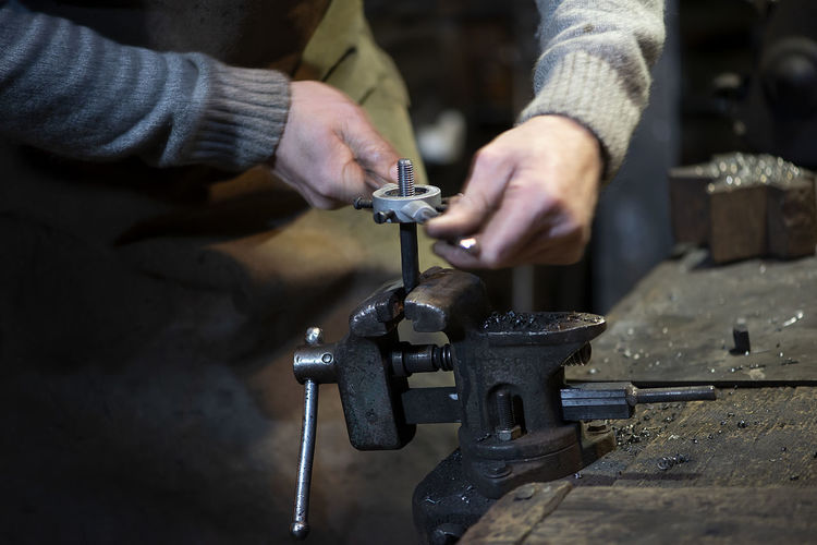 Professional blacksmith working with metal at forge.handmade, craftsmanship , blacksmithing concept