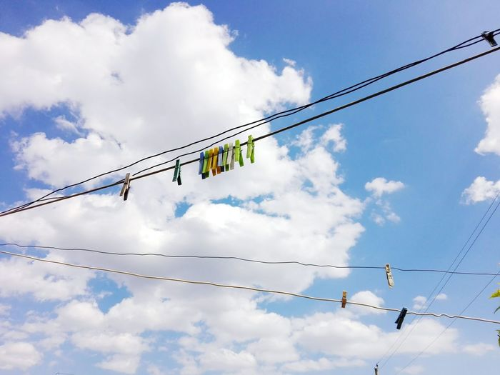 Low angle view of clothespins on clotheslines against cloudy sky