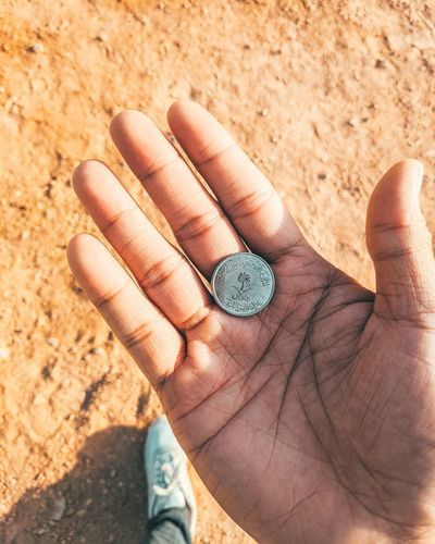 High angle view of human hand holding coin