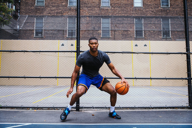 Young man playing basketball against chainlink fence