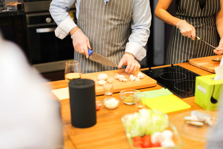 Adult Chef Cutting Cutting Board Domestic Room Food Food And Drink Freshness Hand Holding Human Hand Indoors  Kitchen Kitchen Knife Midsection Mushroom Preparation  Preparing Food Real People Selective Focus Standing Table