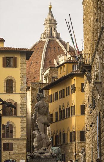 Low angle view of statue and duomo santa maria del fiore in city