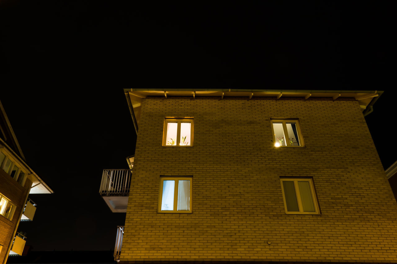 LOW ANGLE VIEW OF ILLUMINATED BUILDING AGAINST CLEAR SKY