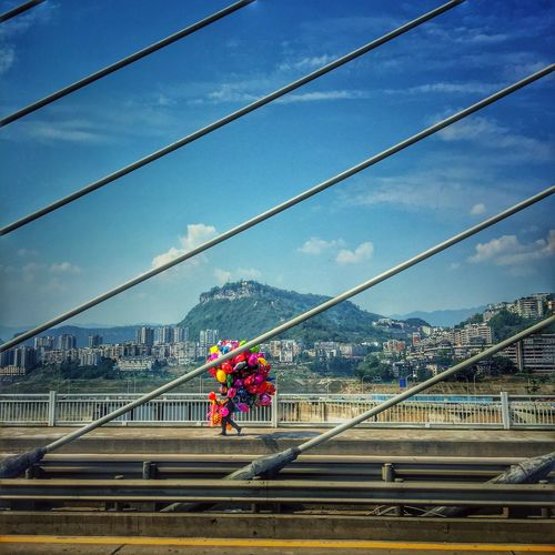 Man carrying balloons on suspension bridge against sky