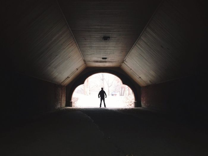 Person Standing At The End of Tunnel