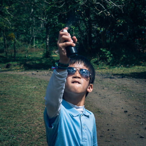 Boy holding perfume sprayer while standing on field