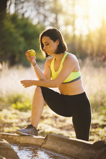 Young sporty woman eating an apple in the field at sunset after running Sporty Woman Sporty Girl Young Woman Crop Top Sportswear Field Runner Yoga Healty Fitness Attractive Sunset Sport Clothes Spring Summer Brunette Leggings Crop Tank Outdoors Lifestyles Exercising Recreational Pursuit Energy Nature Caucasian Athlete One Person Real People Healthy Lifestyle Focus On Foreground Leisure Activity Young Adult Day Holding Sport Sports Clothing Wellbeing Physical Activity Hairstyle Beautiful Woman Clothing Land Plant
