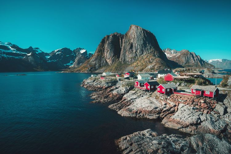 Landscape and red fishing huts at Hamnoy, Lofoten, Norway Water Summer Mountain Outdoors Sea Beach Day Nature No People Sky Beauty In Nature Red Cottage Hut Hamnøy Lofoten Norway