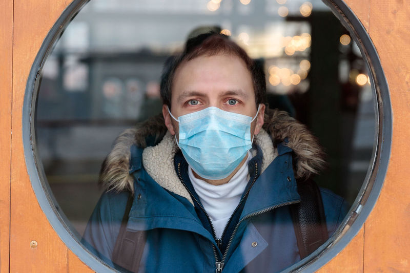 Portrait of man wearing mask seen through window