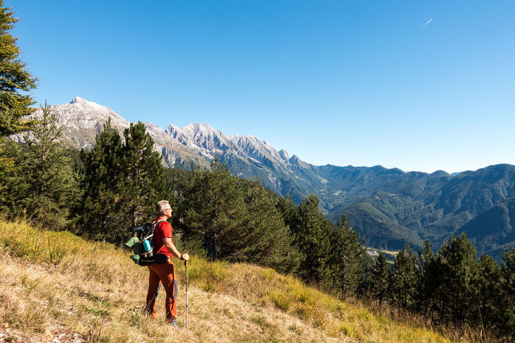 Man hiker is admiring the range mountains landscape. Mountain Leisure Activity Beauty In Nature Plant Sky Scenics - Nature Nature Full Length Activity Mountain Range Adventure One Person Clear Sky Healthy Lifestyle Non-urban Scene Lifestyles Hiking Outdoors Hiking Hiker Sport