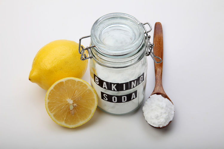 baking soda in the glass container with lemon Alkaline Anti Inflammatory Baking Soda Bicarbonate Cleaner Close-up Cooking Glass Container Heart Burn Ingredient Jar Label Lemon Medicine Neutralizer Portrait Sodium Bicarbonate Spoon Spoonful Spoonfull White Background Wooden Spoon