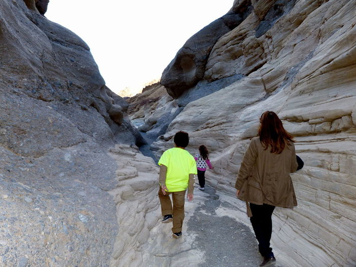 Rear View Of Mother Walking With Children Amidst Slot Canyon