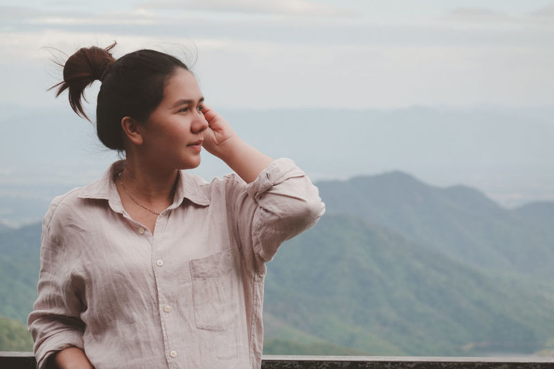 Young woman looking at mountains against sky