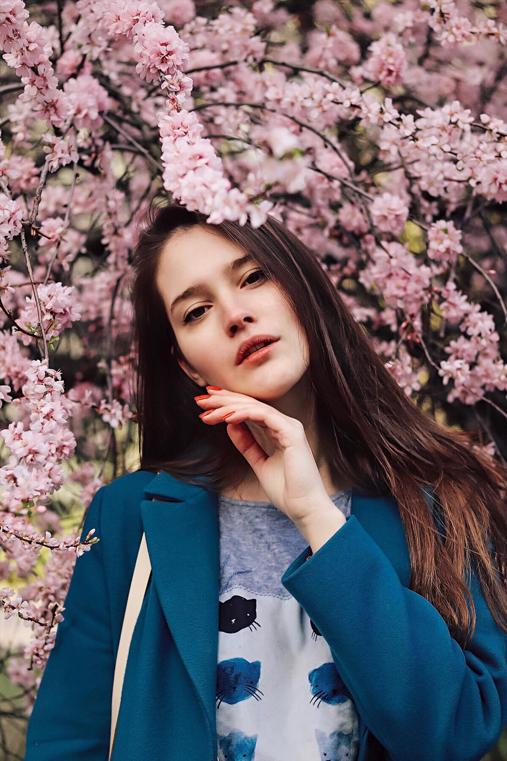 one person, flower, young adult, flowering plant, real people, portrait, plant, lifestyles, front view, young women, long hair, beauty, hairstyle, leisure activity, women, hair, nature, fragility, beautiful woman, beauty in nature, pink color, outdoors, springtime, cherry blossom