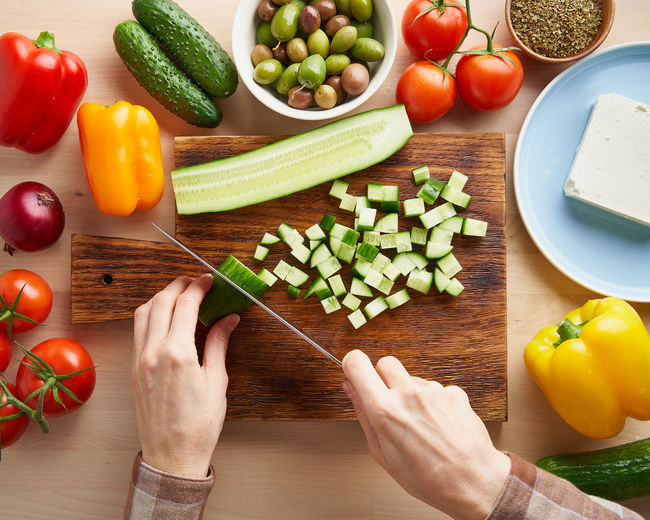 Step by step recipe for salad horiatiki, wooden board for cutting vegetables and ingredients. hands