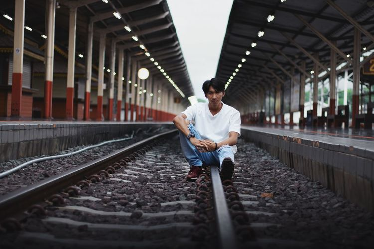 Full length of man sitting on railroad track
