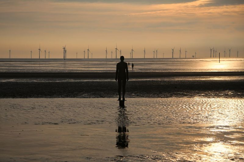 Crosby Beach Sky Scenics - Nature Water Beauty In Nature Sea Nature Crosby Beach Sunset Beach Standing Rear View Real People Land Cloud - Sky One Person Reflection Silhouette Orange Color Tranquility Full Length Horizon Over Water