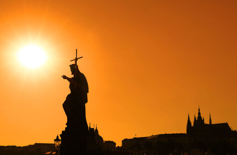 Low Angle View Of Silhouette John The Baptist Statue Against Clear Sky During Sunset