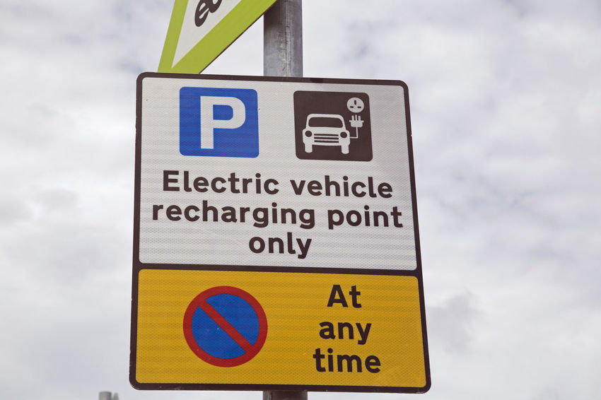 Sign advises that electric vehicle charging is available Capital Letter Close-up Cloud - Sky Communication Day Guidance Information Information Sign Nature No People Number Outdoors Road Sign Sign Sky Symbol Text Warning Sign Western Script Yellow