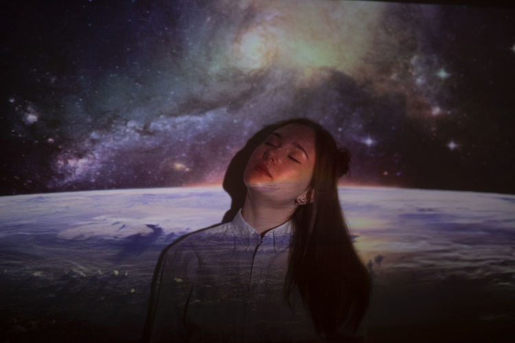 Portrait of smiling young woman against sky at night