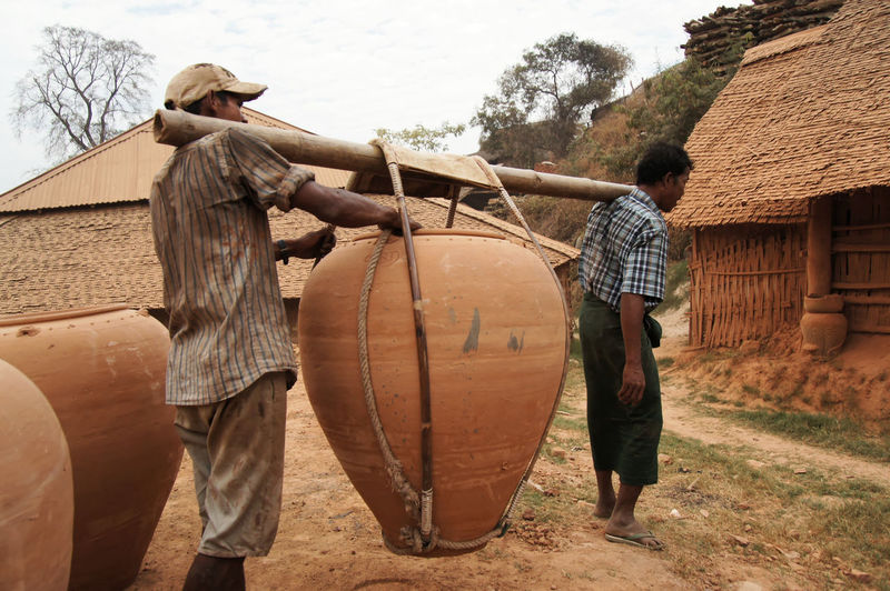 Traveling the upper Irrawaddy, Kyaukmyaung, Myanmar Agriculture Architecture Barrel Building Exterior Day Field Full Length Hard Labor Men Myanmar Occupation Outdoors People Real People Rear View Standing Street Photography Togetherness Tree Wine Cask Working Young Adult