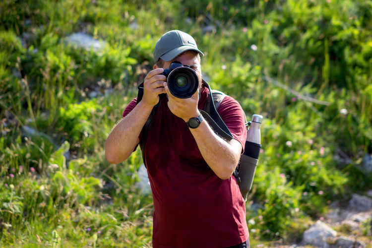 Mountain hiker photographer explores the area for the photographic hunting of wild animals.