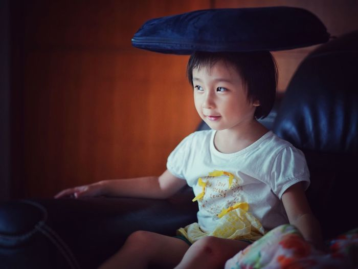 Cute Girl Balancing Cushion On Head While Sitting At Home