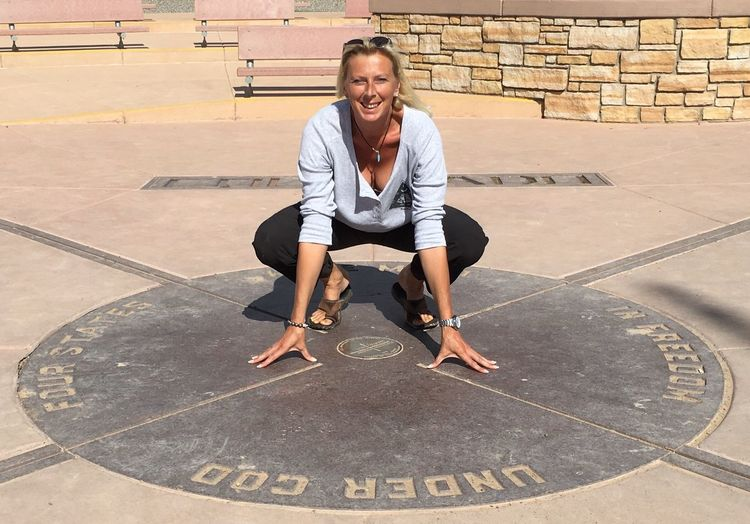 Full length portrait of happy woman crouching at four corners monument