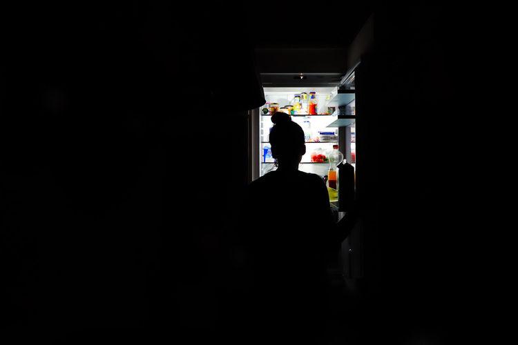 Silhouette teenage girl standing by refrigerator