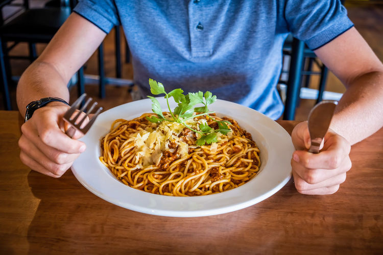 Midsection of man having pasta in plate on table in the restaurant holding utencils