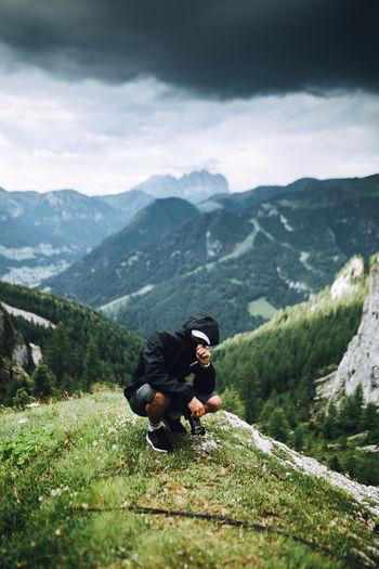 Man wearing hoodie crouching against mountain range