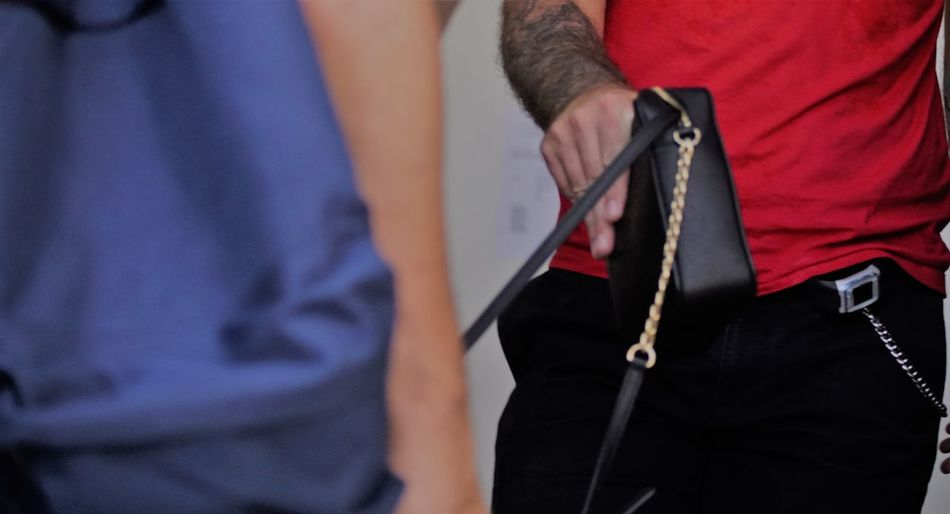 Middle section of a man holding a lady handbag. Care and polite concept. Adult Anonymous Confidence  Elegant Fashion Bag Black Casual Clothing Caucasian Close-up Clothing Colleague Communication Concept Control Cropped Detail Executive  Fashionable Holding Human Body Part Men Midsection Standing Tattoo