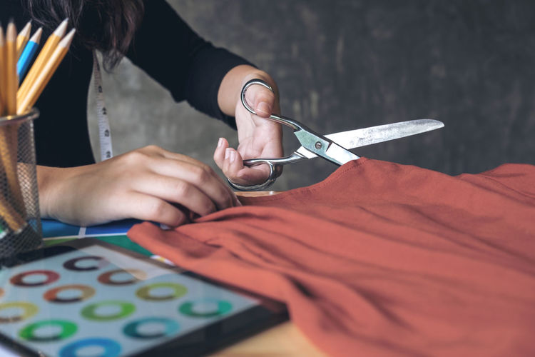 Cropped image of fashion designer cutting red fabric at desk