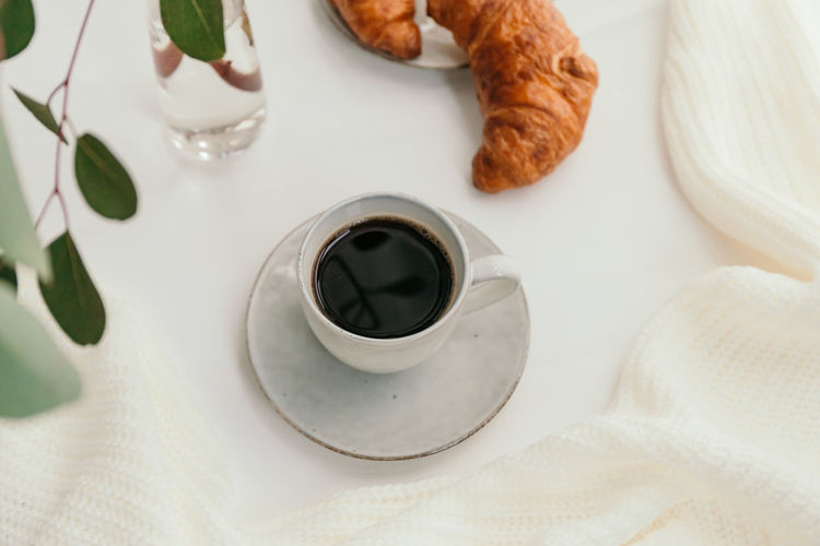 Cup of black coffee with croissant on white table. The concept of breakfast. Coffee Croissant Breakfast Morning Cup Cappuccino Background Drink Pastry Table Latte Cafe Espresso White Hot Americano Caffeine Bread Food Dessert Fresh Brown Rustic Break Linen Minimalist Minimal Cotton Beige Golden Atmosphere Sweet Above Composition Ceramics Mug Black Beverage Time Food And Drink Coffee - Drink