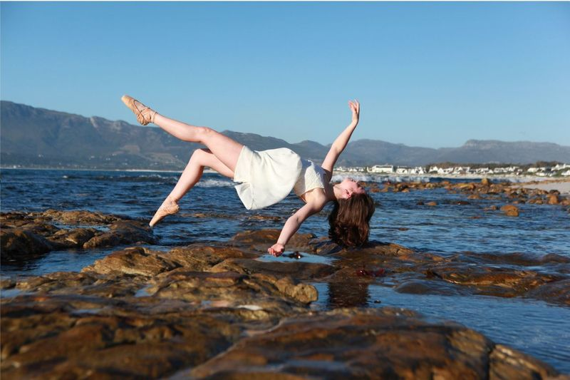 Full length of young woman levitating at beach