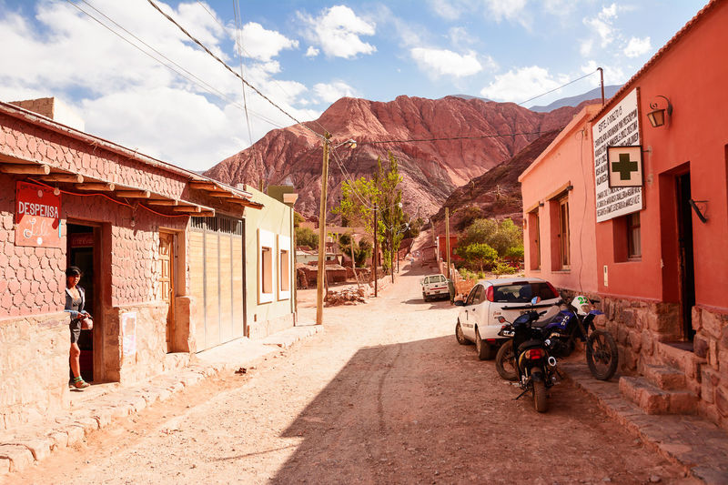 Purmamarca, Argentina - November 1, 2016: Street in Purmamarca with indigen woman and car (Argentina) Andes Argentina Car Cerro Cerro De Los 7 Colores Cerro De Los Siete Colores Cerro De Los Siete Colores En Jujuy City Colors Hill Of Seven Colours Humahuaca Jujuy Landscape Motocycle Motorcycle Outdoors Purmamarca Quebrada Rescue Road Seven Shop Street Unpaved Village