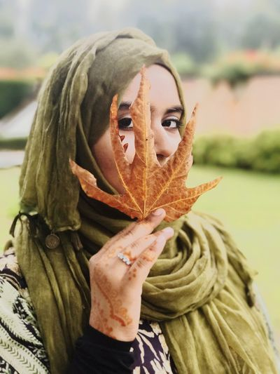 Close-up portrait of young woman in hijab holding leaf