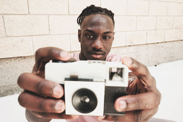 Portrait Photography Themes One Person Holding Young Adult Looking At Camera Real People Front View Young Men Technology Photographing Camera - Photographic Equipment Lifestyles Headshot Wall - Building Feature Leisure Activity Men Wall Activity Hand Brick